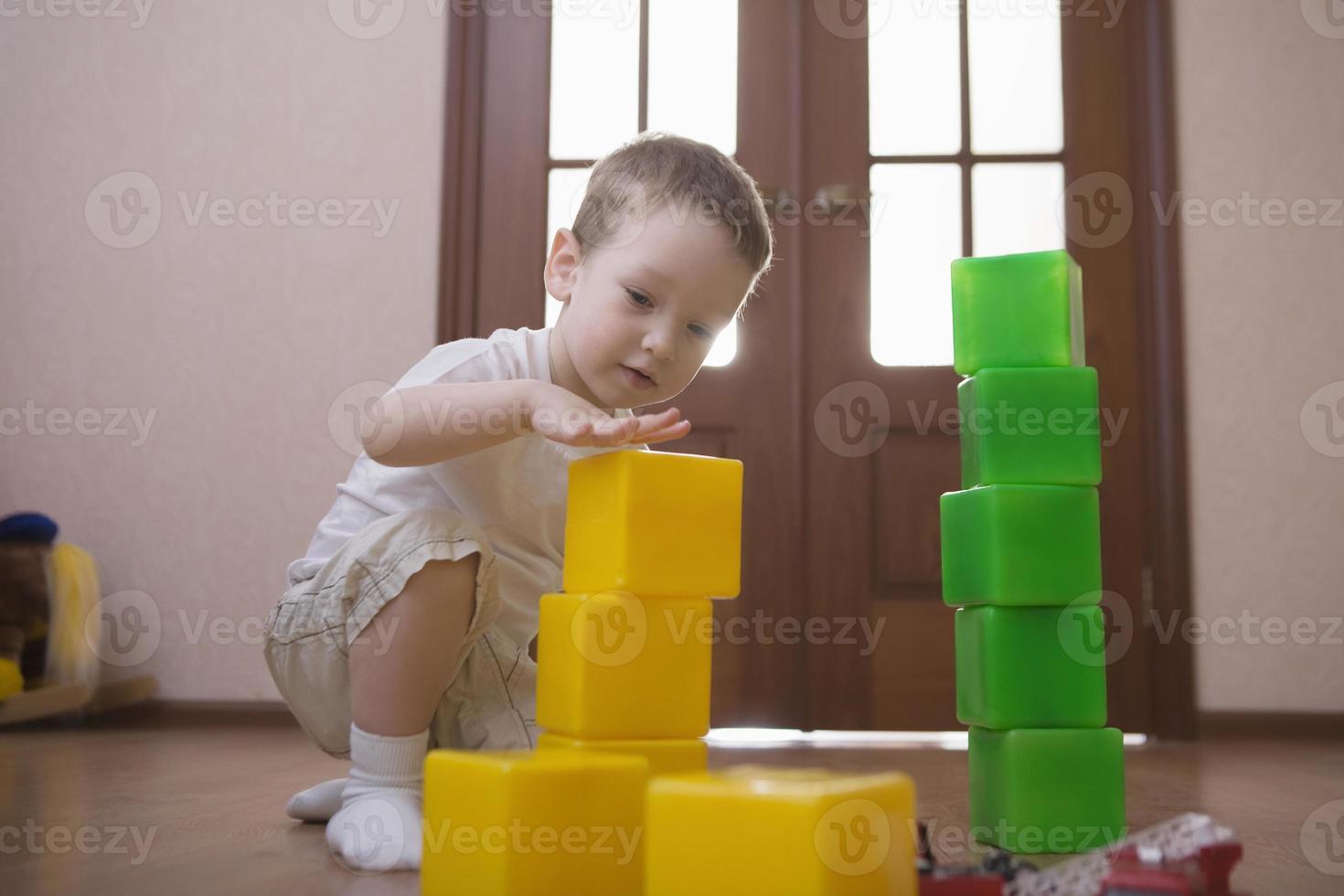 pojke bygger torn från färgglada kuber foto