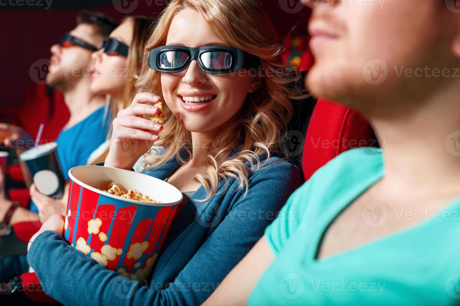 kvinna i 3 d glas som äter popcorn foto