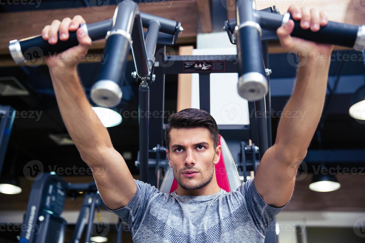 man gör övning på fitness maskin i gymmet foto