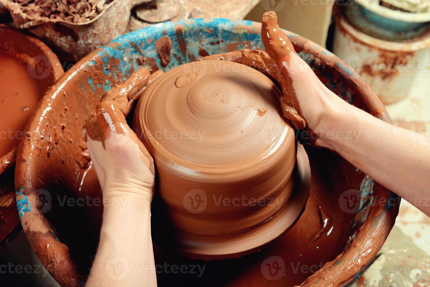 händerna på en keramiker som skapar en lerkrukan foto
