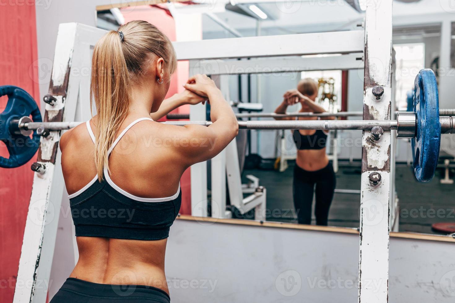 fitness kvinna förbereder skivstång knäböj i ett gym foto