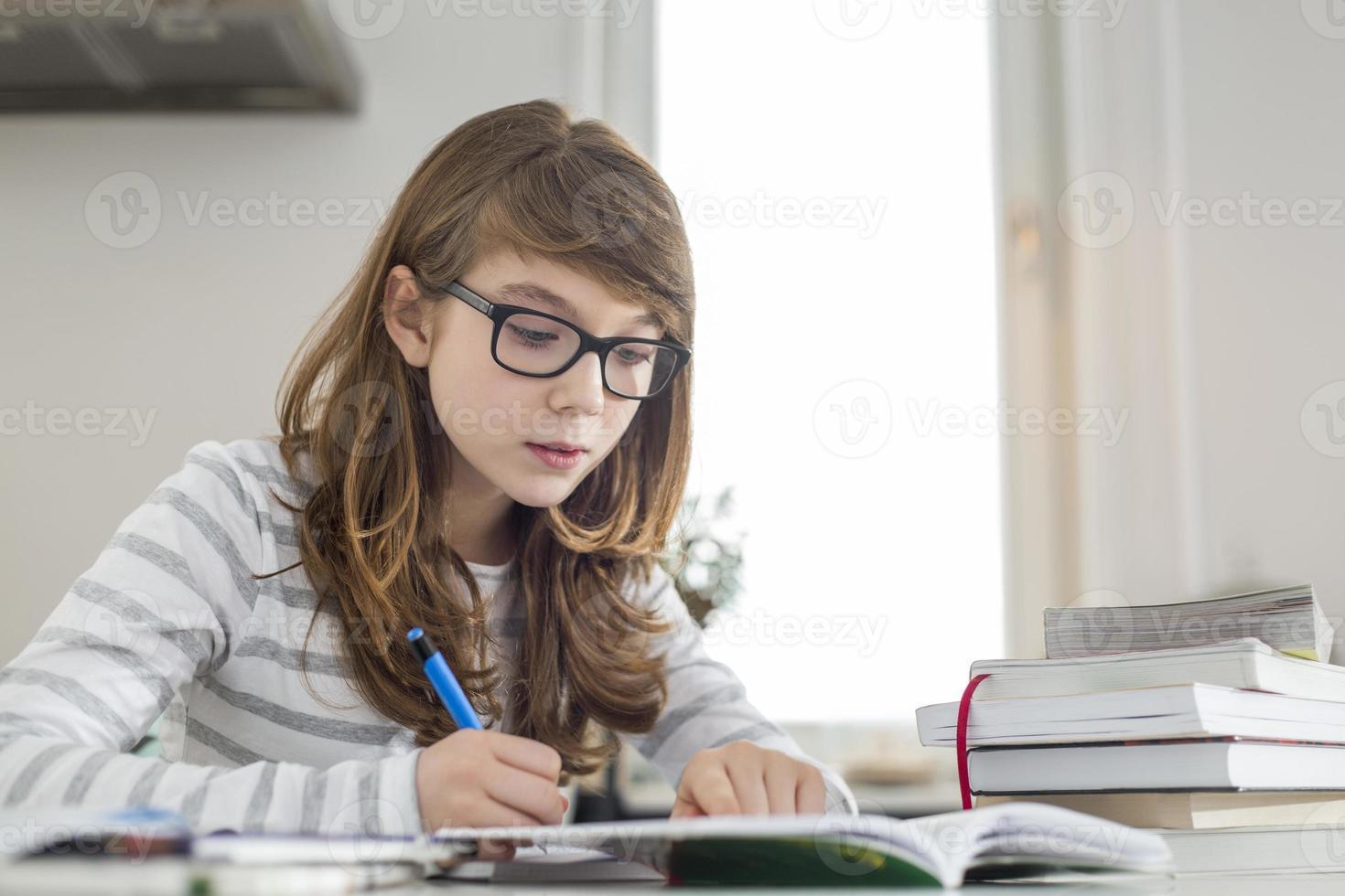 tonårsflicka som gör läxor vid bordet foto