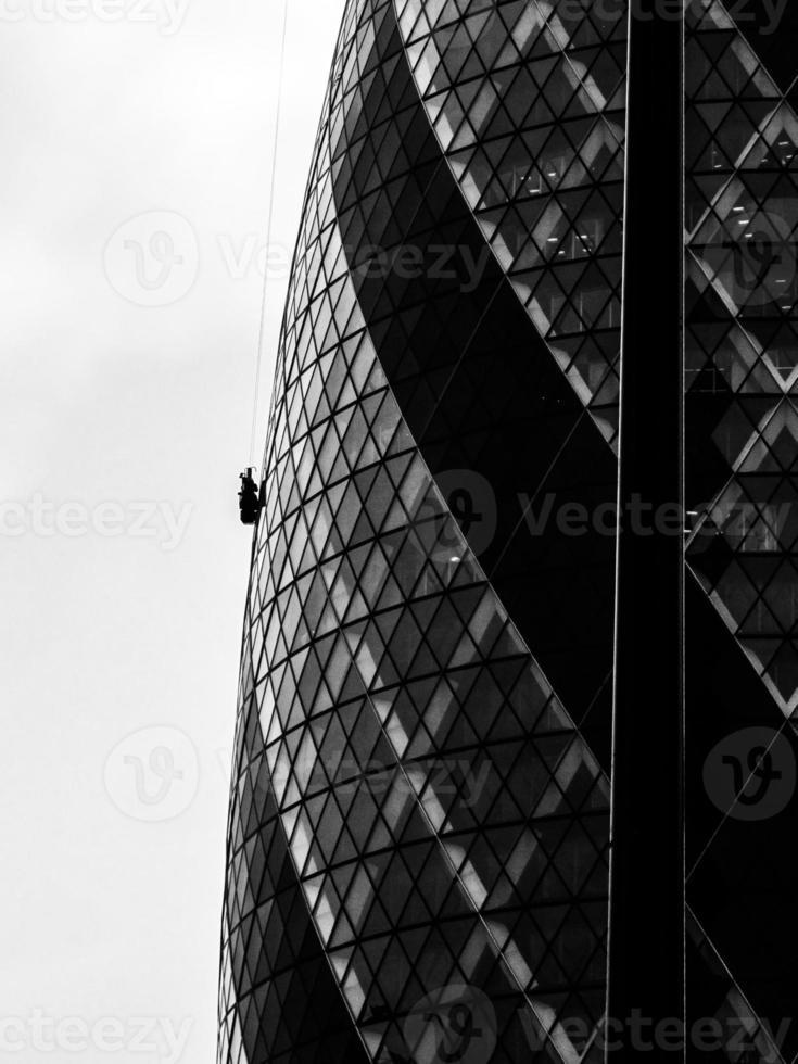 fönsterrengörare extremt hängande på högbyggnadsglasbyggnad foto