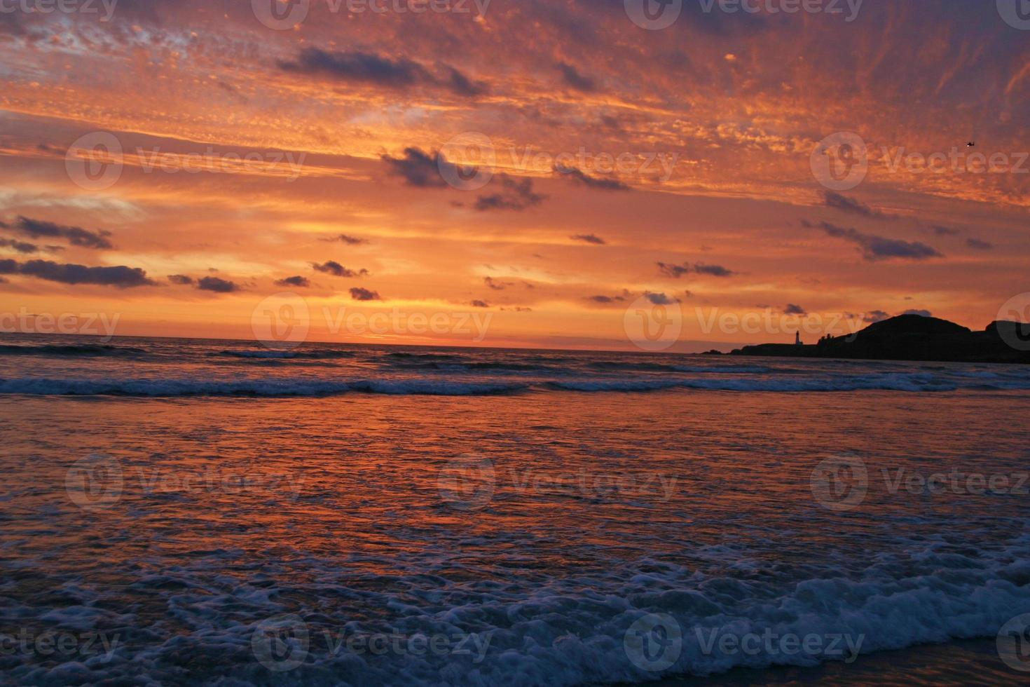 härlig solnedgång över fyr och hav foto