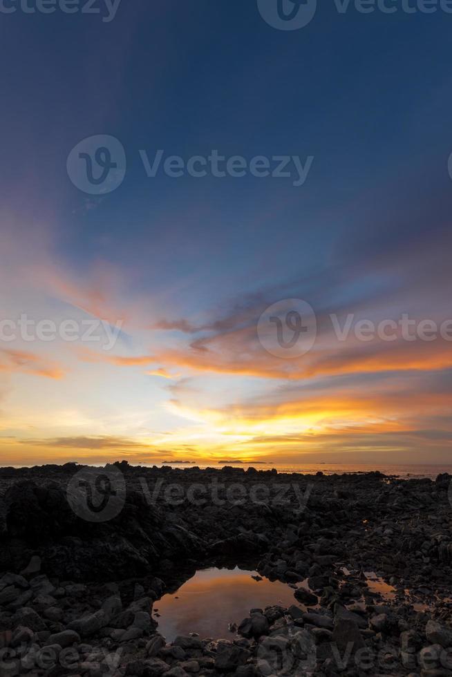 litet damm på stenig strand vid solnedgången. foto