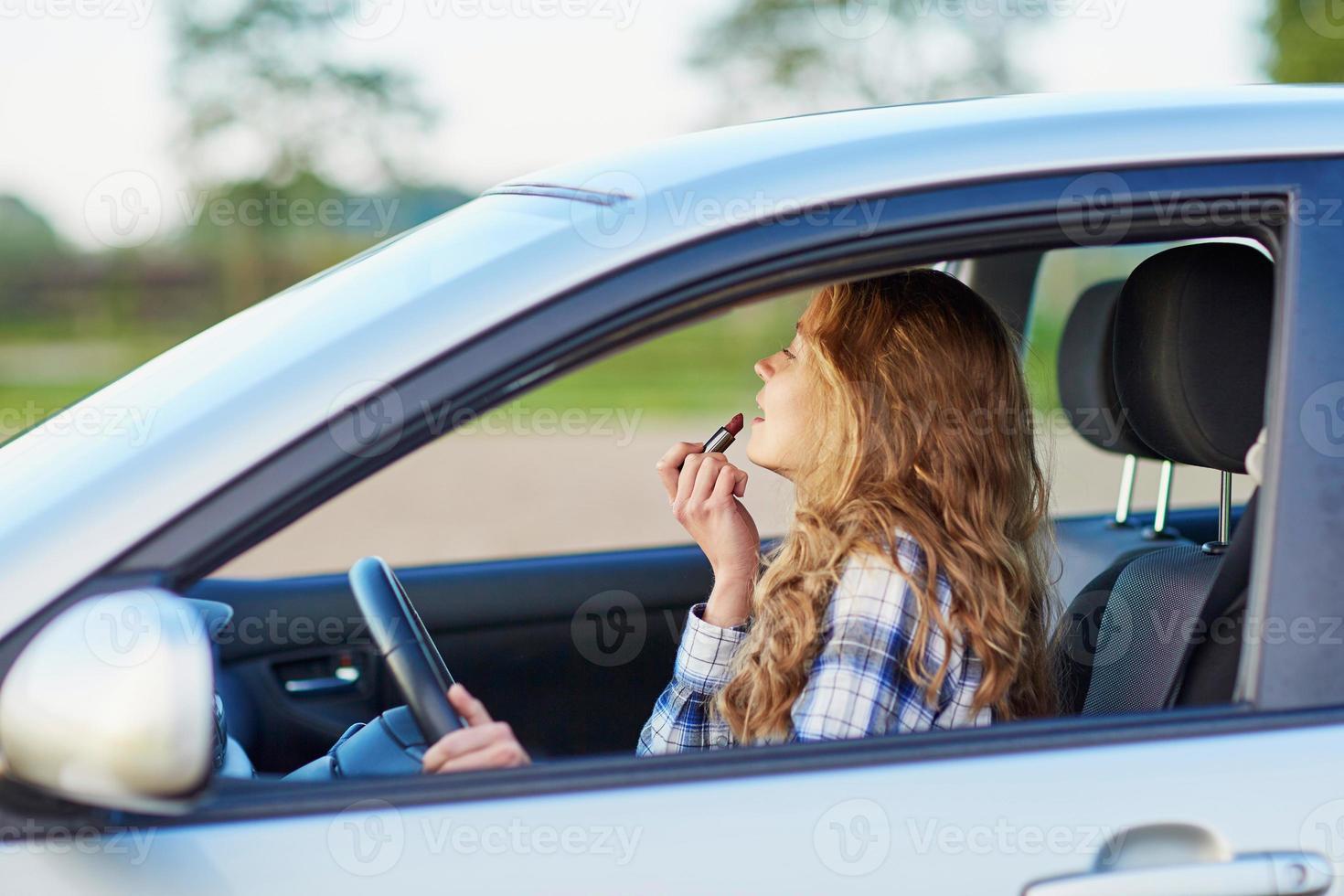 kvinna som applicerar läppstift i en bil under körning foto