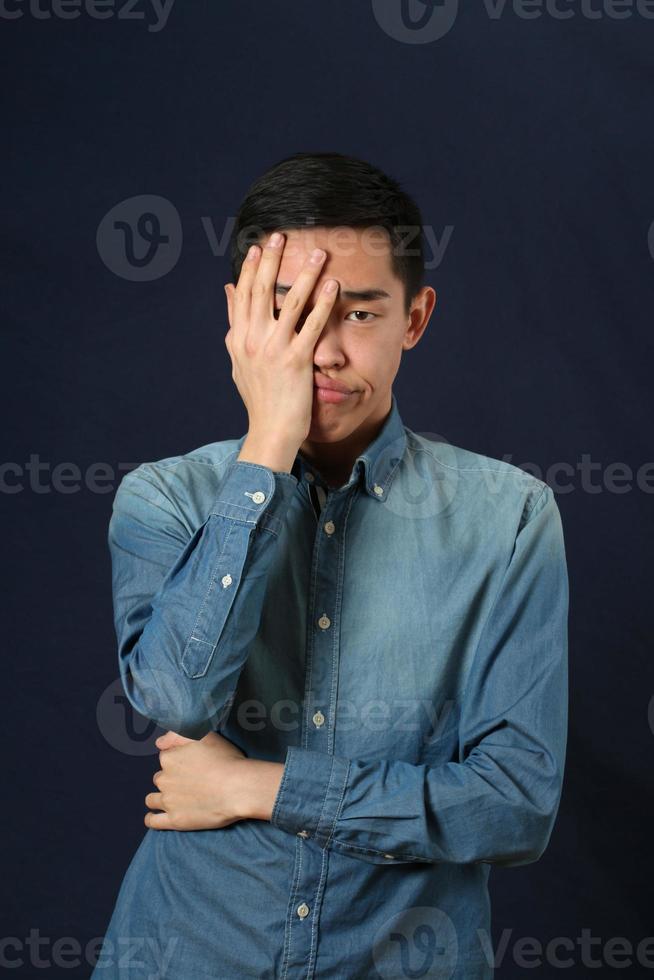 besviken ung asiatisk man som täcker ansiktet med handflatan foto