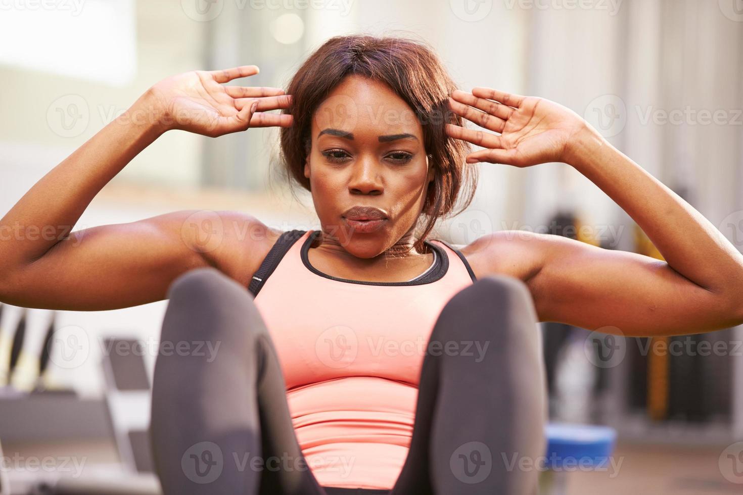 ung kvinna gör crunches i ett gym, närbild foto