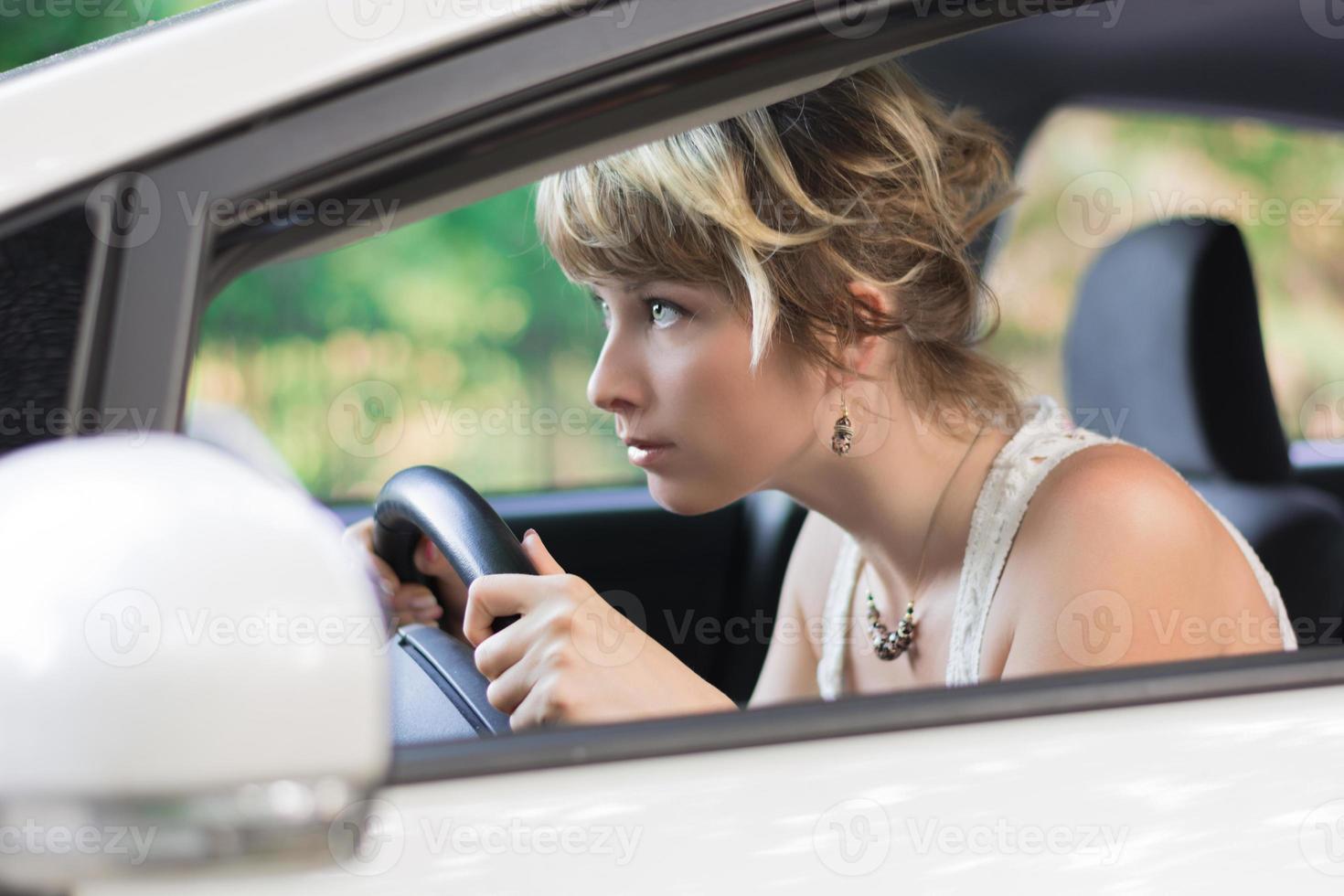 ung kvinna som lär sig att köra bil och luta sig framåt foto
