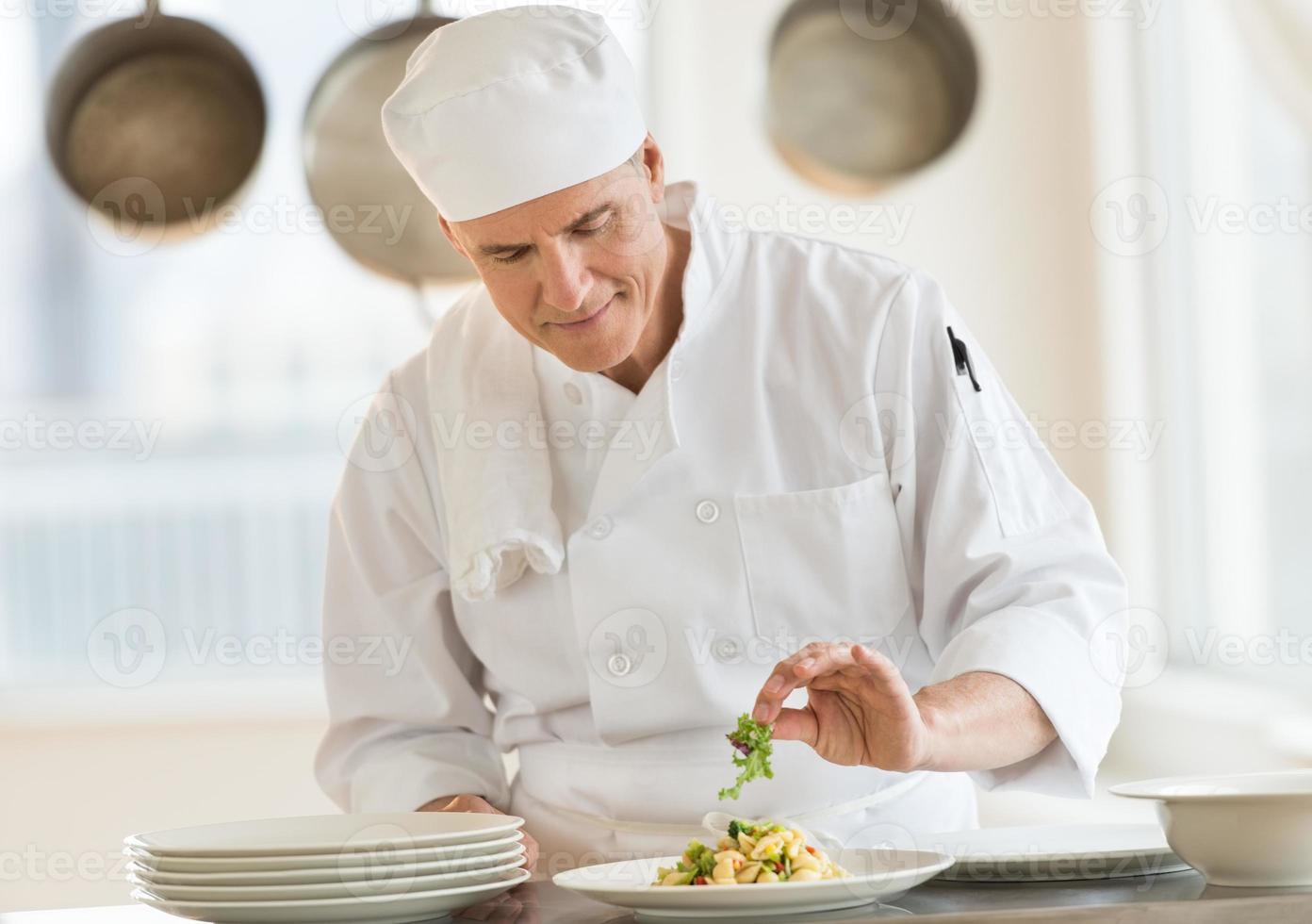kock som garnerar maträtt i kommersiellt kök foto