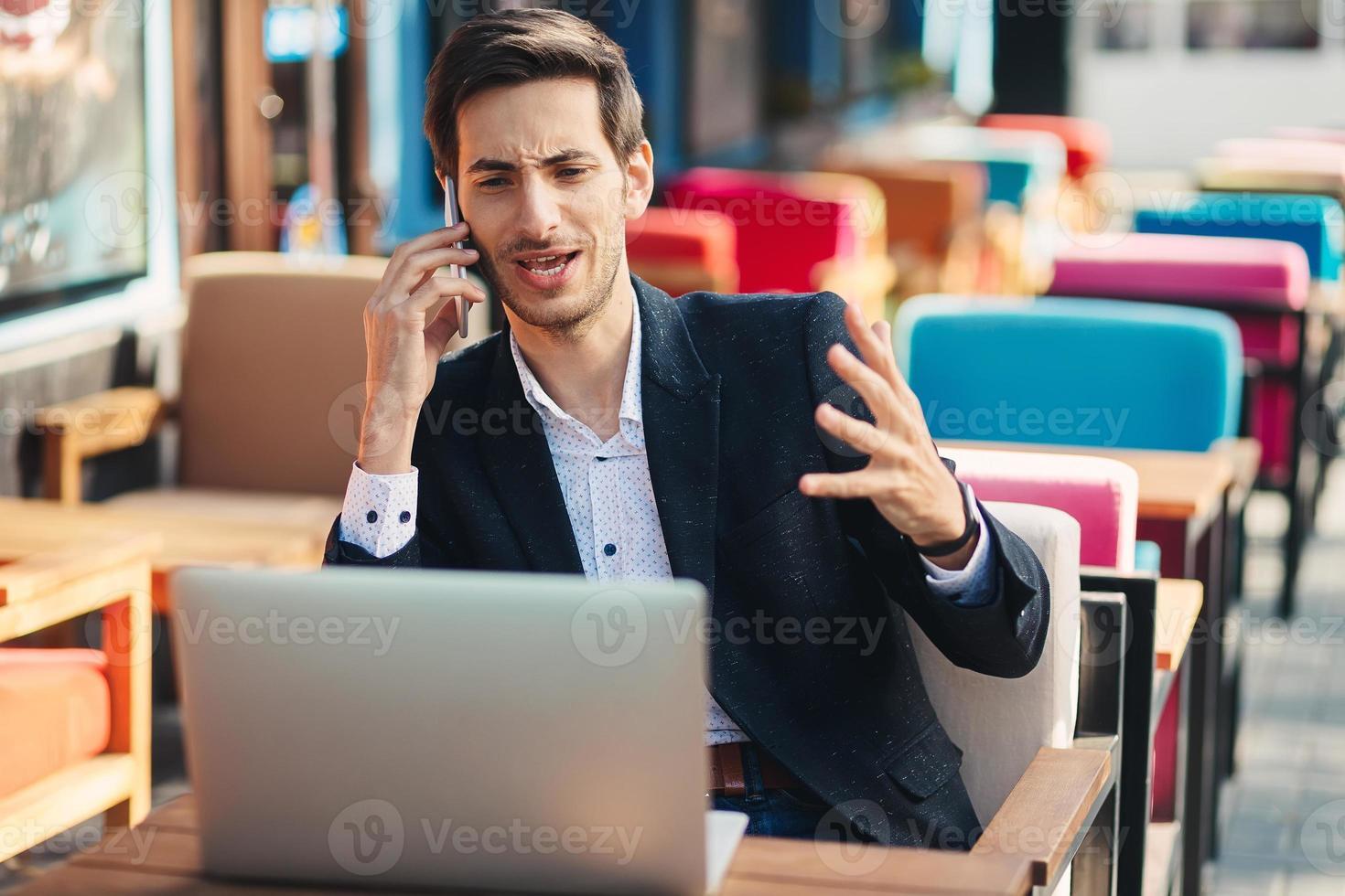 ung entreprenör som arbetar på bärbar dator och telefon foto