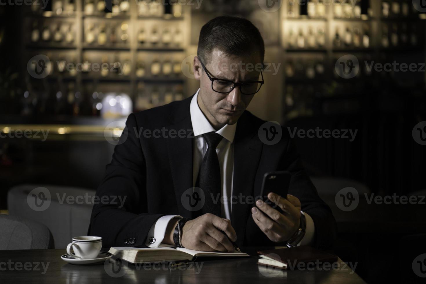 porträtt av allvarlig stilig elegant kaukasisk affärsman som sitter på den moderna restaurangen som kontrollerar sin smarta telefon och skriver anteckningarna i sin anteckningsbok foto