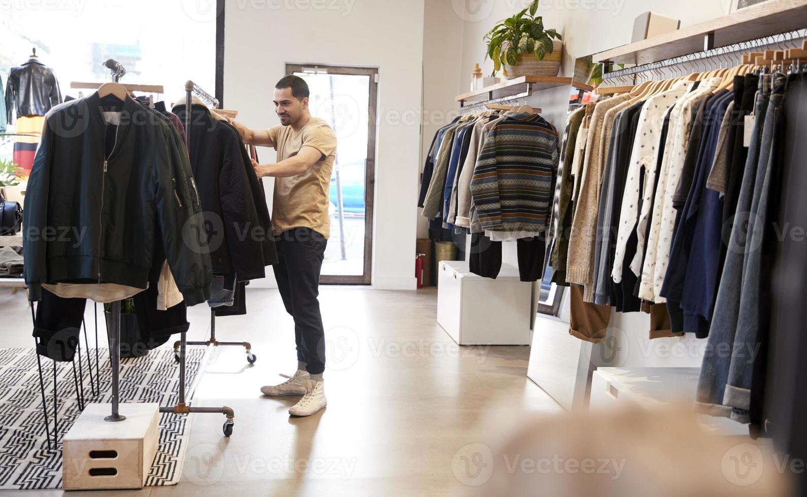 ung latinamerikansk man tittar på kläder i en klädbutik foto