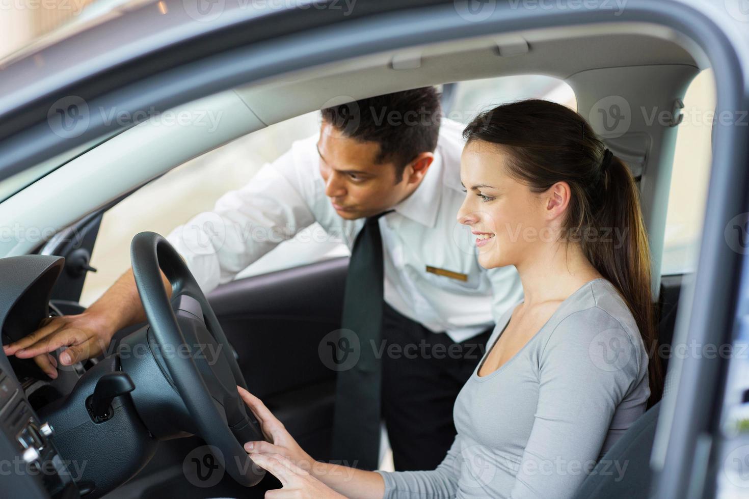 säljare som förklarar bilens funktioner till kunden foto