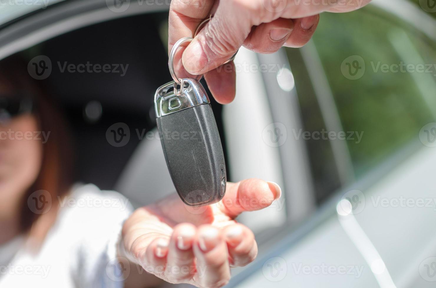 man som ger bilnyckel till en kvinna foto