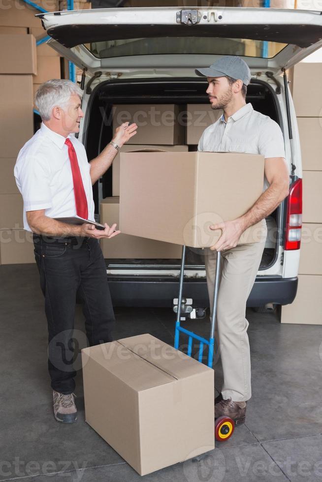 lagerchef och leveransförare som pratar bredvid skåpbilen foto