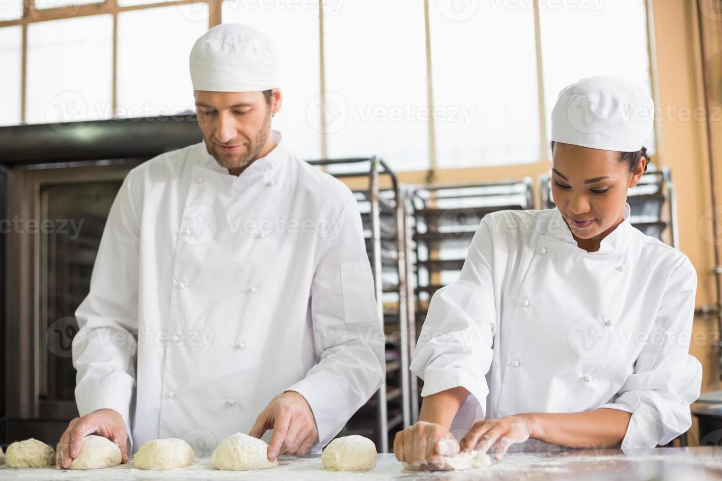 team av bagare som förbereder degen foto
