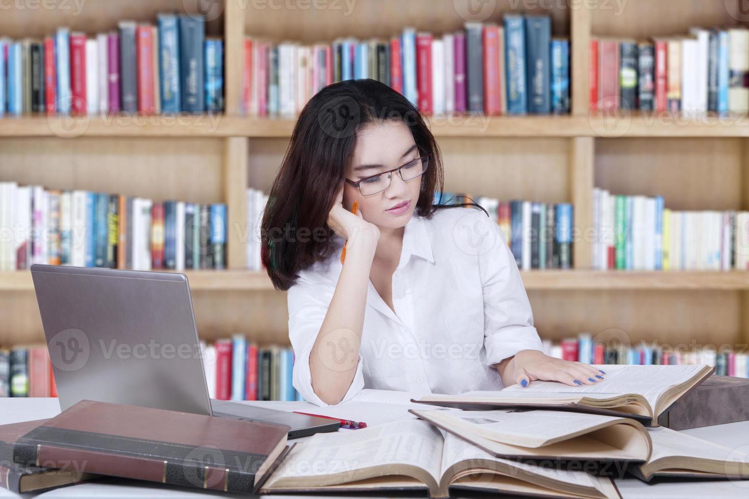 student som sitter i biblioteket medan han läser böcker foto