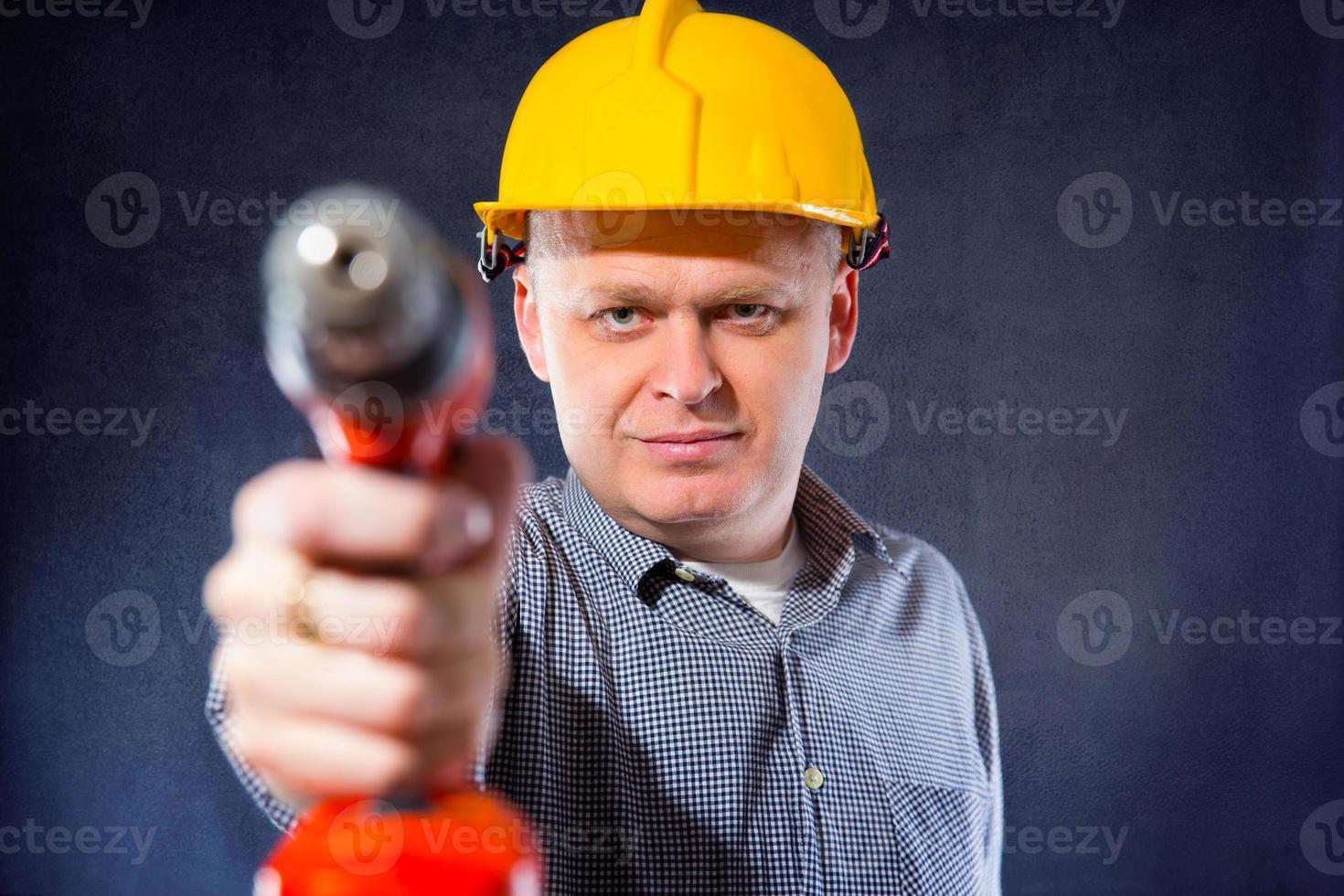 byggnadsarbetare som håller en borr foto