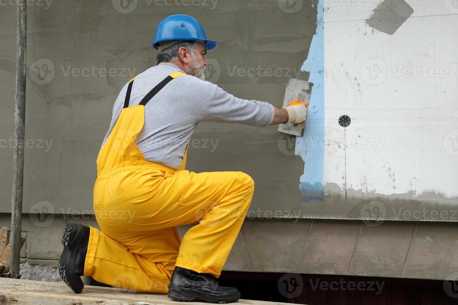 väggisolering, spridande murbruk över nät och styrofoam foto