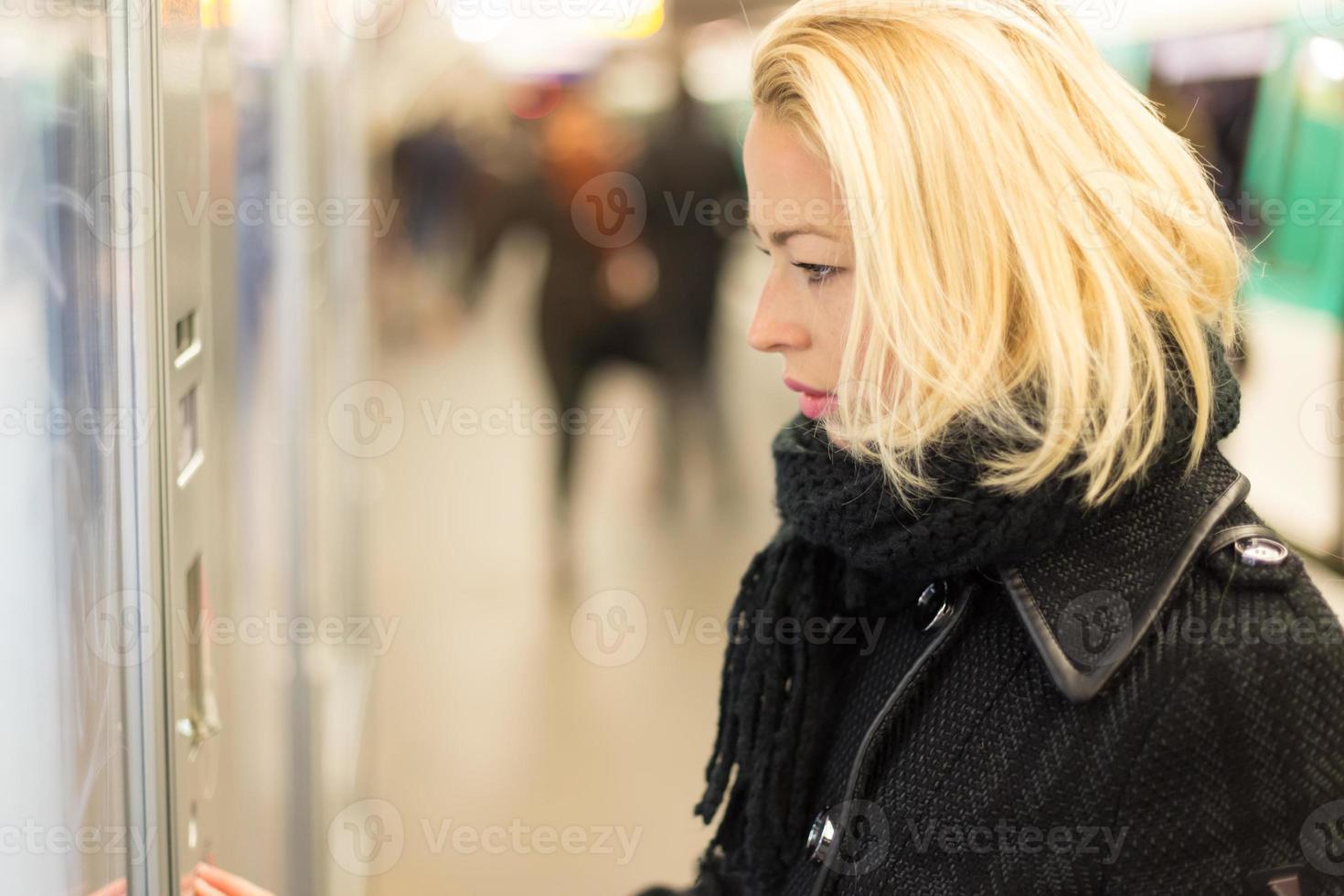 dam som köper biljett för kollektivtrafik. foto