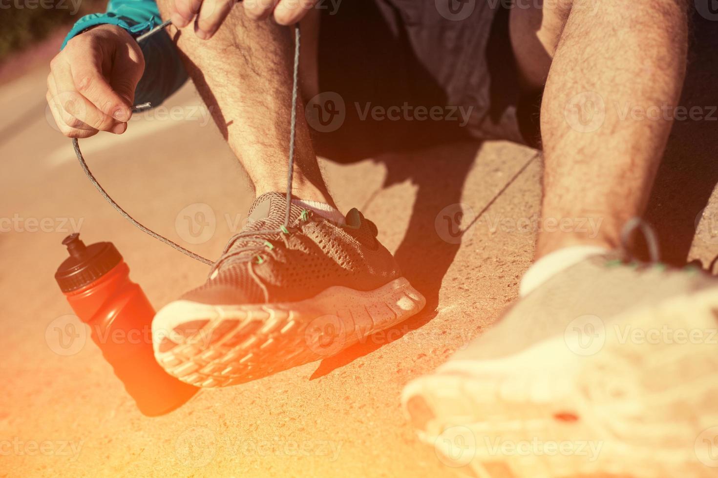 idrottsman slipsskor på sina löparskor i parken foto