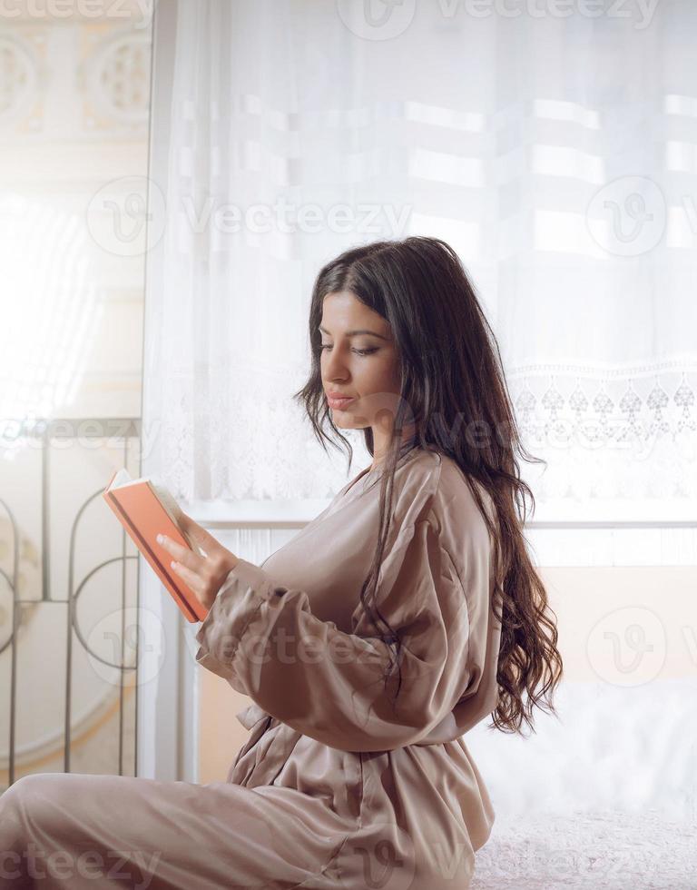 elegant tjej som läser en bok i lägenheten foto