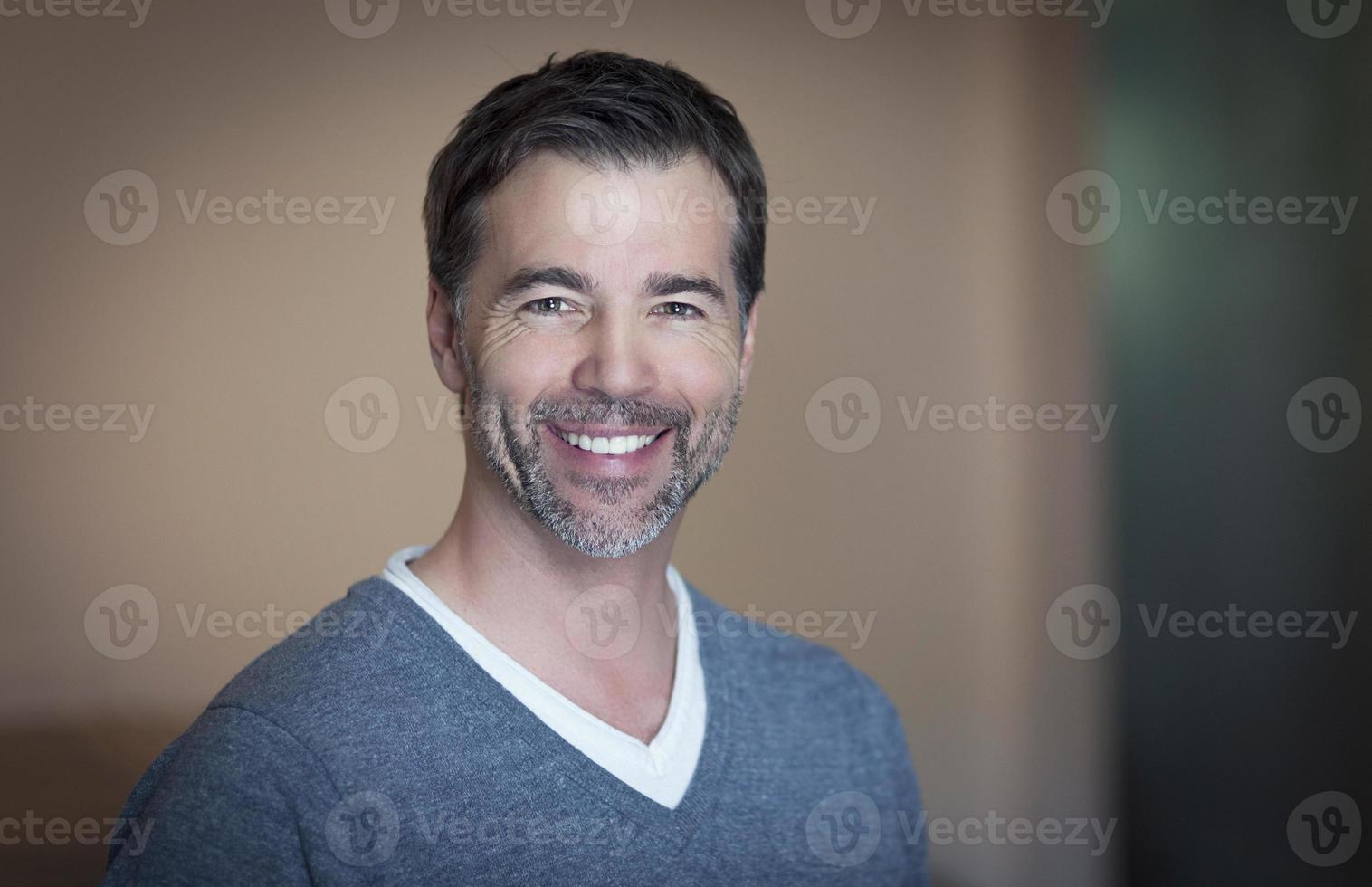 närbild av en mogen man som ler hemma foto