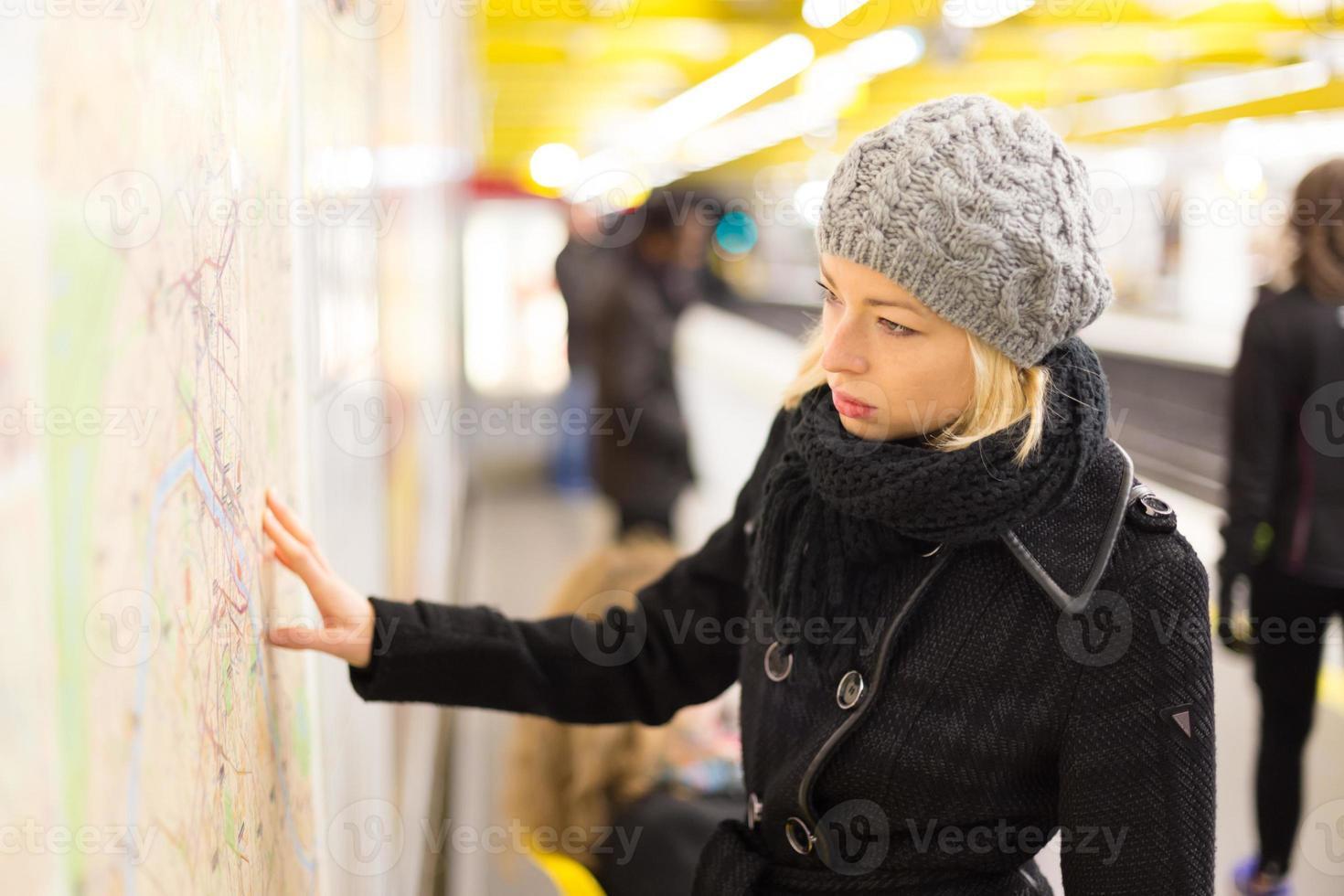 dam som tittar på kartan med kollektivtrafik. foto