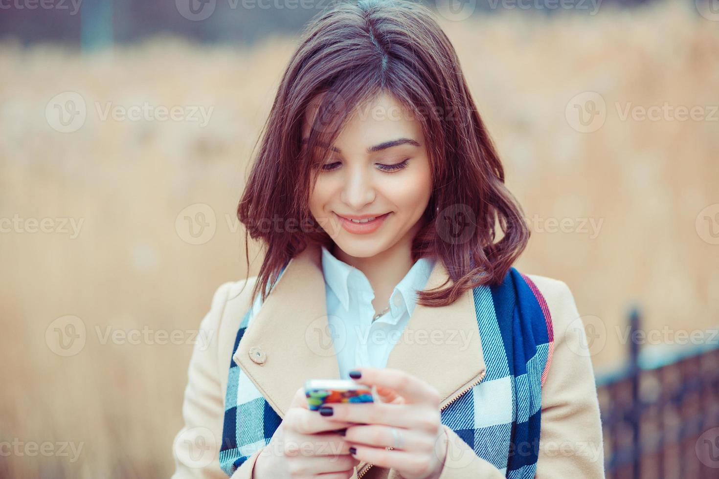 kvinna sms. närbild ung glad le gladlynt vacker kvinna tittar på mobiltelefon läsning skicka sms isolerade park stadsbild utomhus bakgrund. positivt ansiktsuttryck mänskliga känslor foto