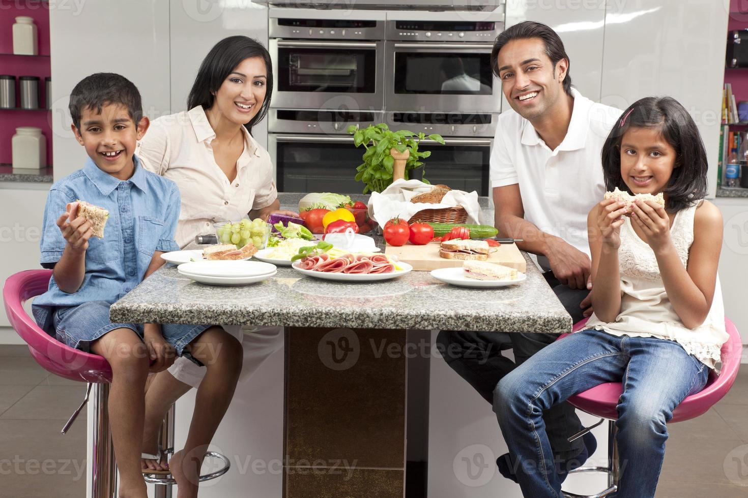 asiatiska indiska föräldrar barnfamilj äter hälsosam mat i köket foto
