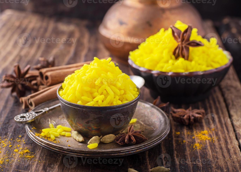 ljusgul kokt ris med gurkmeja och aromatiska kryddor på foto