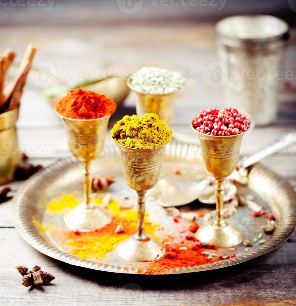 olika indiska kryddor i vintage metallkoppar foto