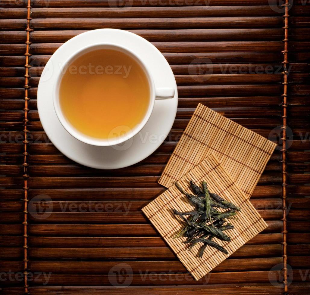 kopp bryggt grönt te med bambuunderlägg foto