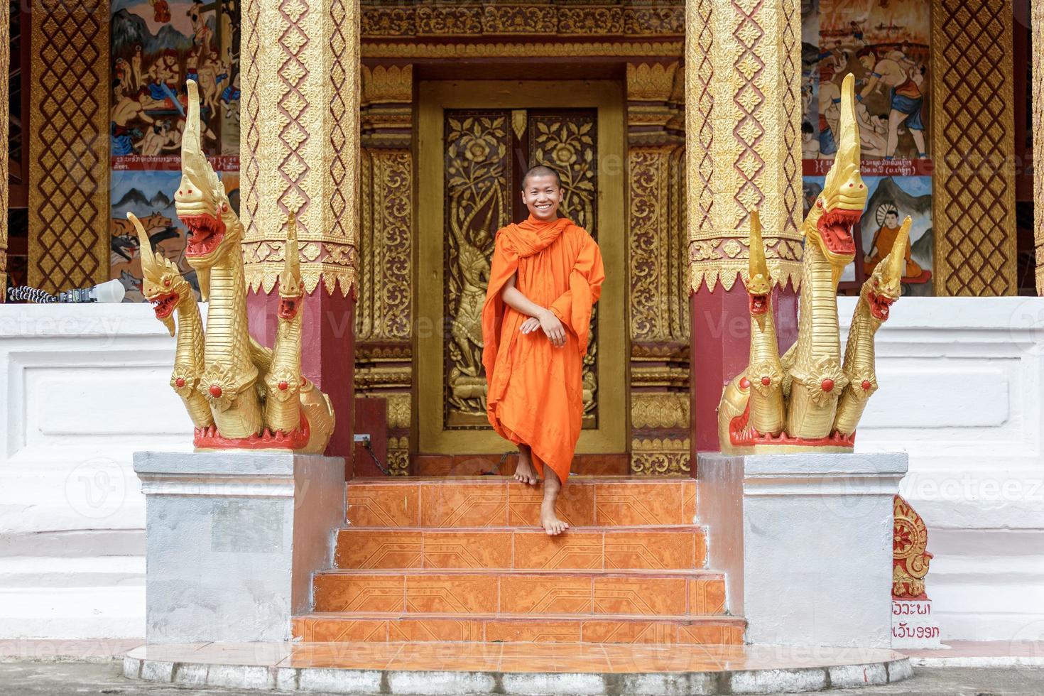 ung buddhistisk munk som går framför klostret foto