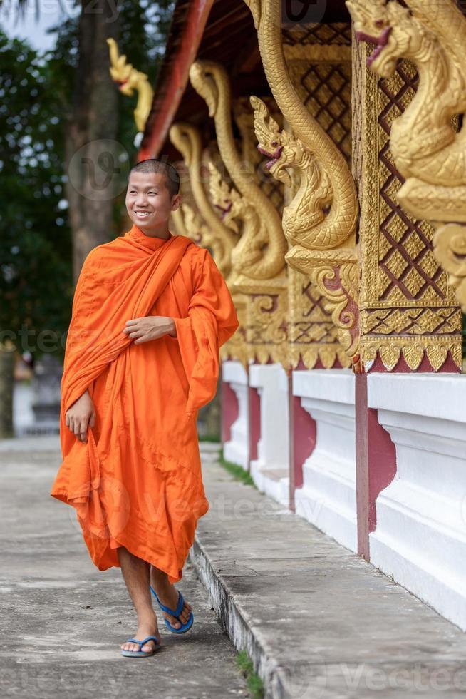 ung buddhistisk munk som går bredvid templet foto