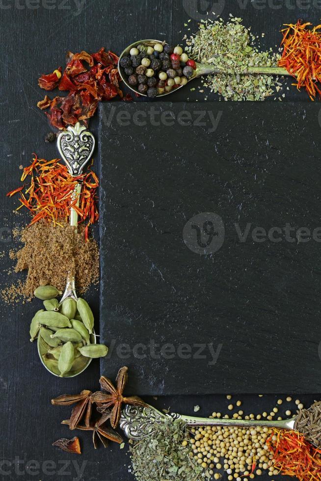olika kryddor (paprika, gurkmeja, peppar, anis, kanel, saffran) foto