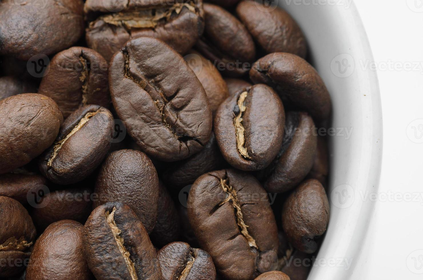 rostade organiska kaffebönor i vitmugg foto
