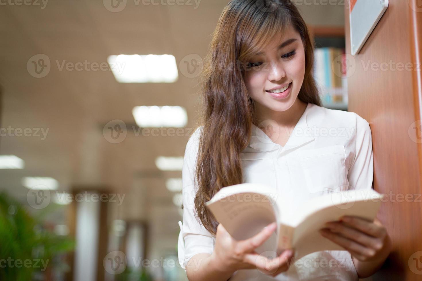 vacker asiatisk kvinnlig student läser bok i biblioteket foto
