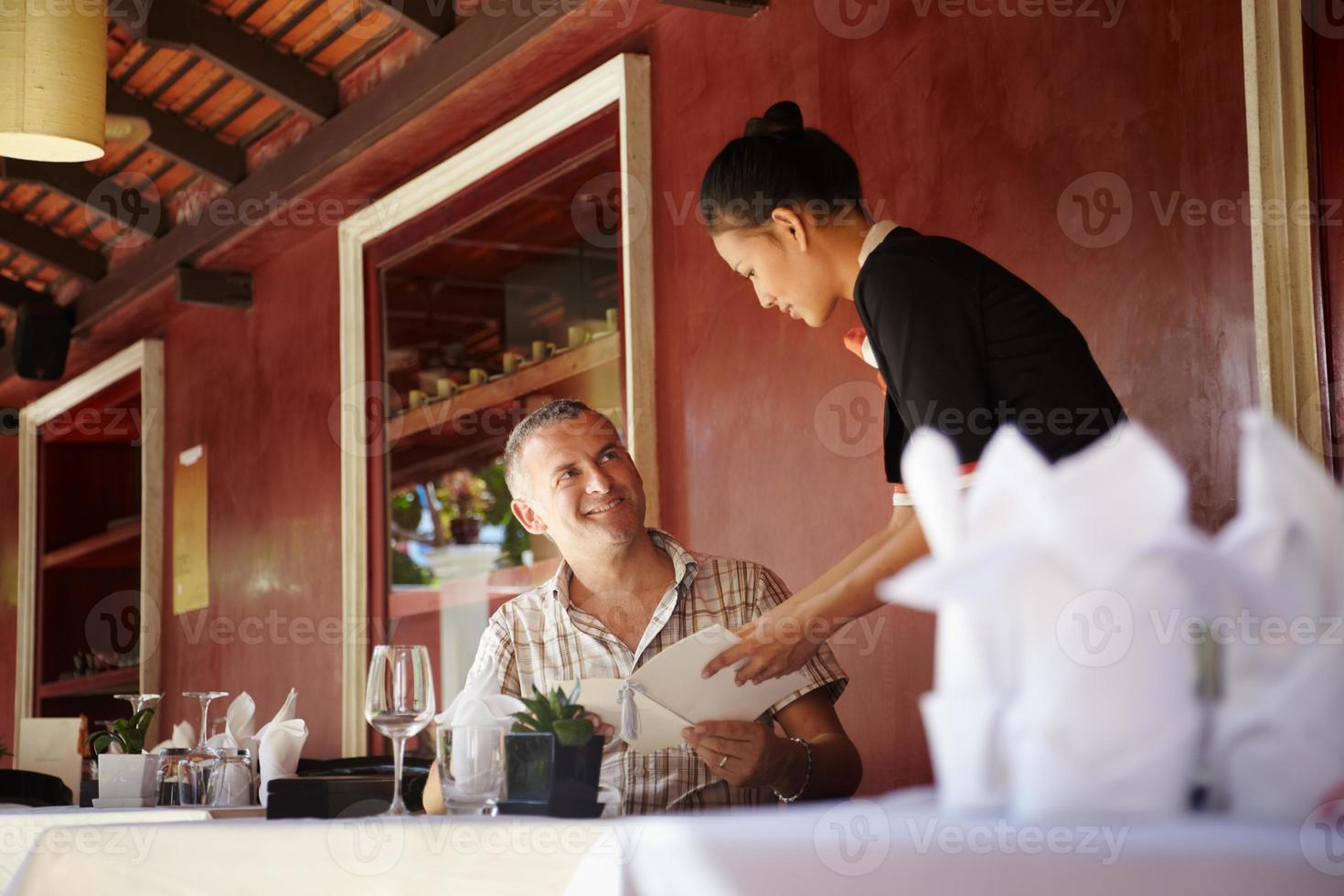 asiatisk servitris som pratar med klienten i restaurangen foto