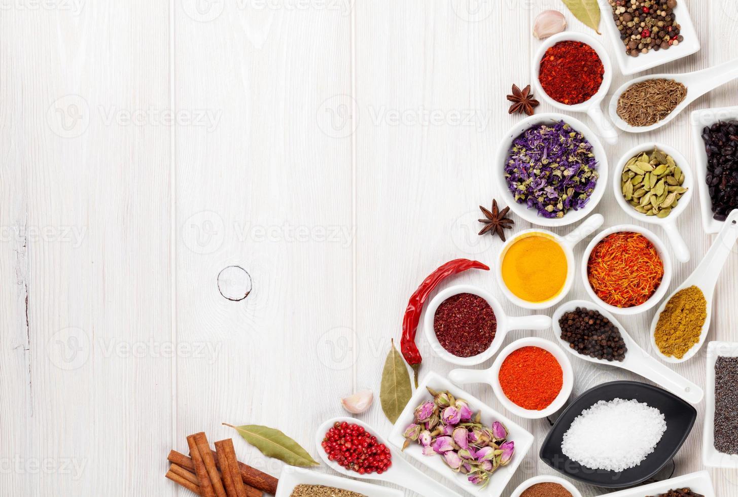 olika kryddor på vit träbakgrund foto