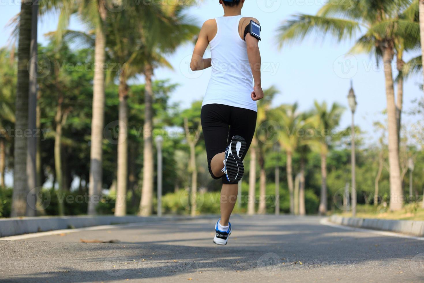 kvinna löpare kör på tropiska park trail foto