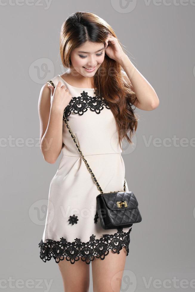 asiatisk kvinna veckad ärmlös spets rand klänning svart-sling väska. foto