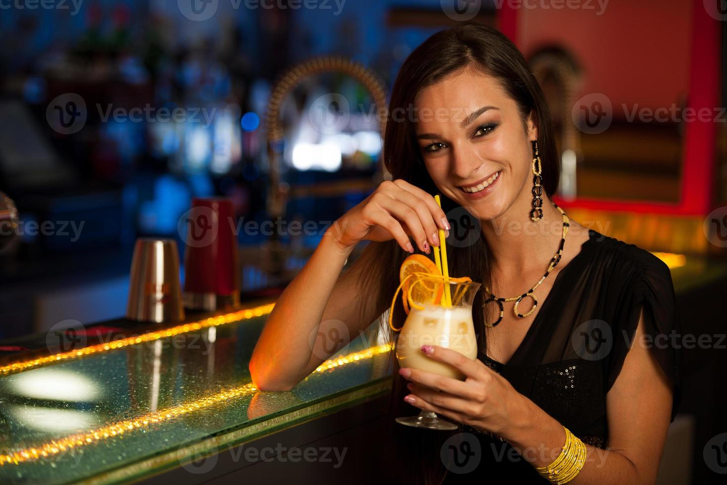 flickan dricker en cocktail i nattklubben foto