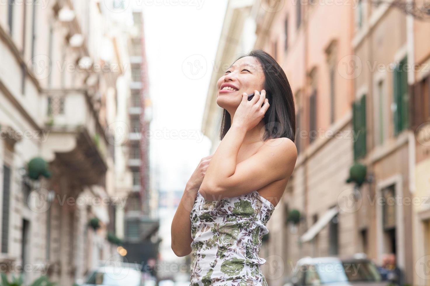 vacker asiatisk kvinna leende med mobiltelefon våren urban utomhus foto