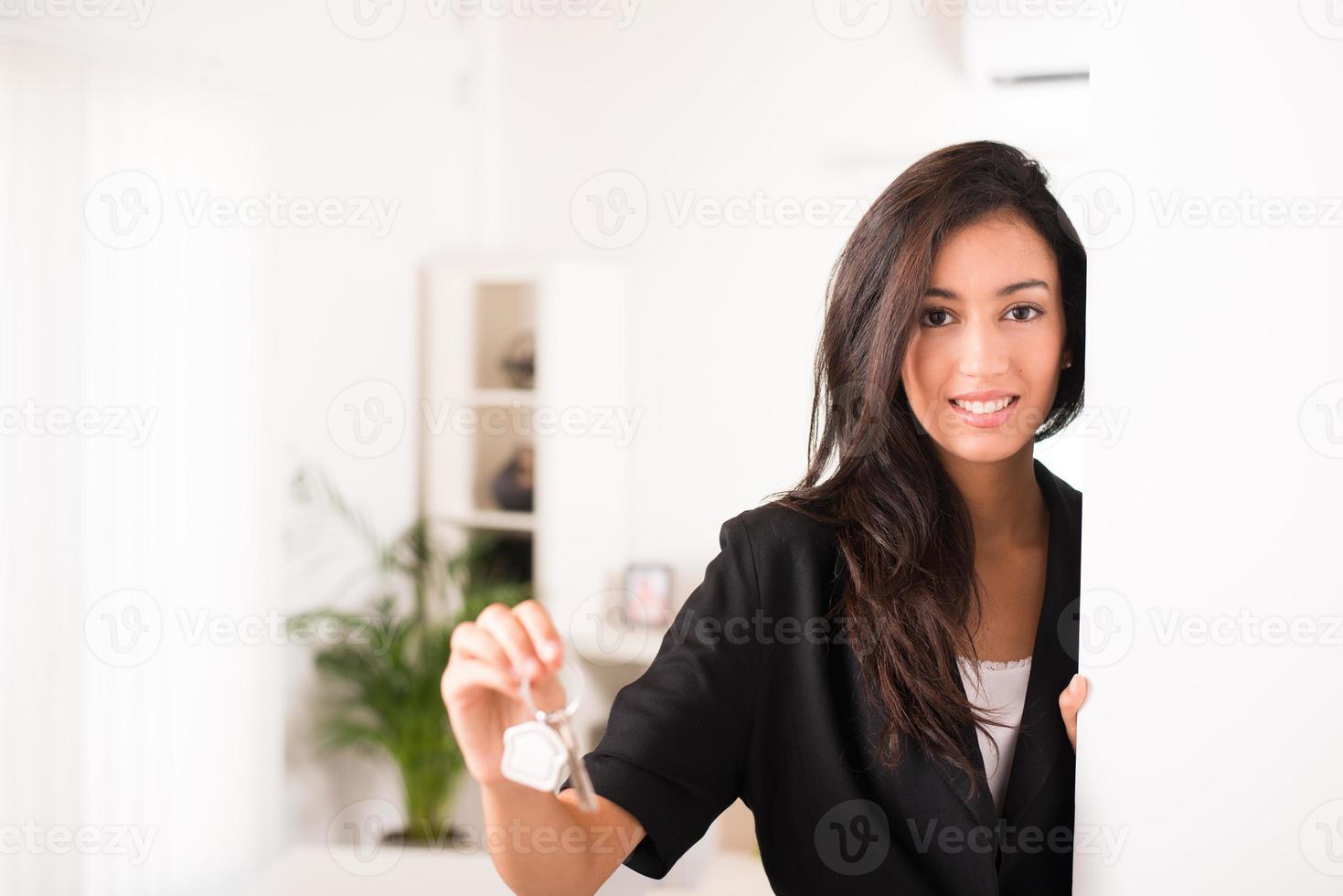 glad ung affärskvinna fastighetsmäklare som ger nycklar nytt hus foto