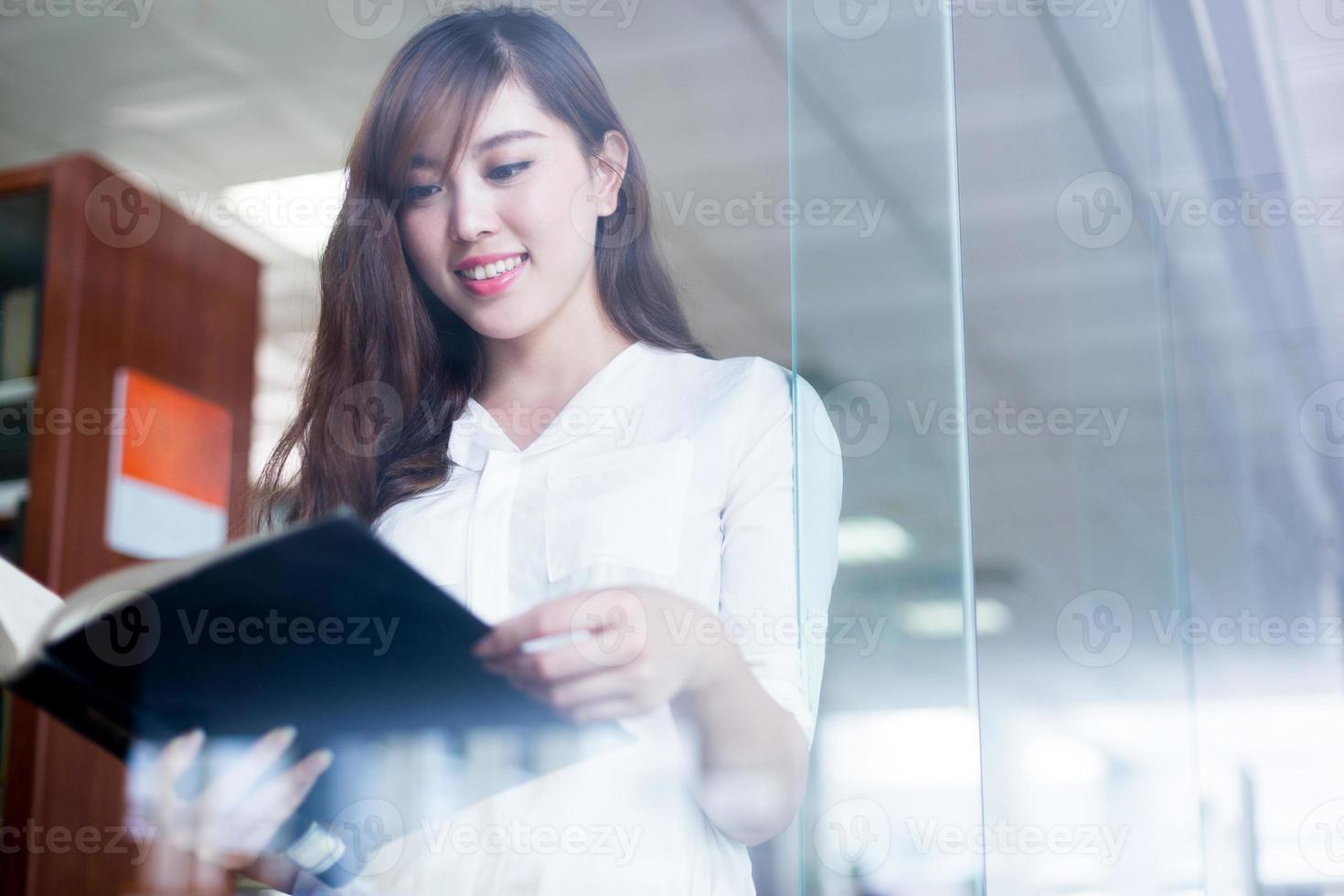 asiatisk vacker kvinnlig studentinnehavbok i biblioteksporträtt foto