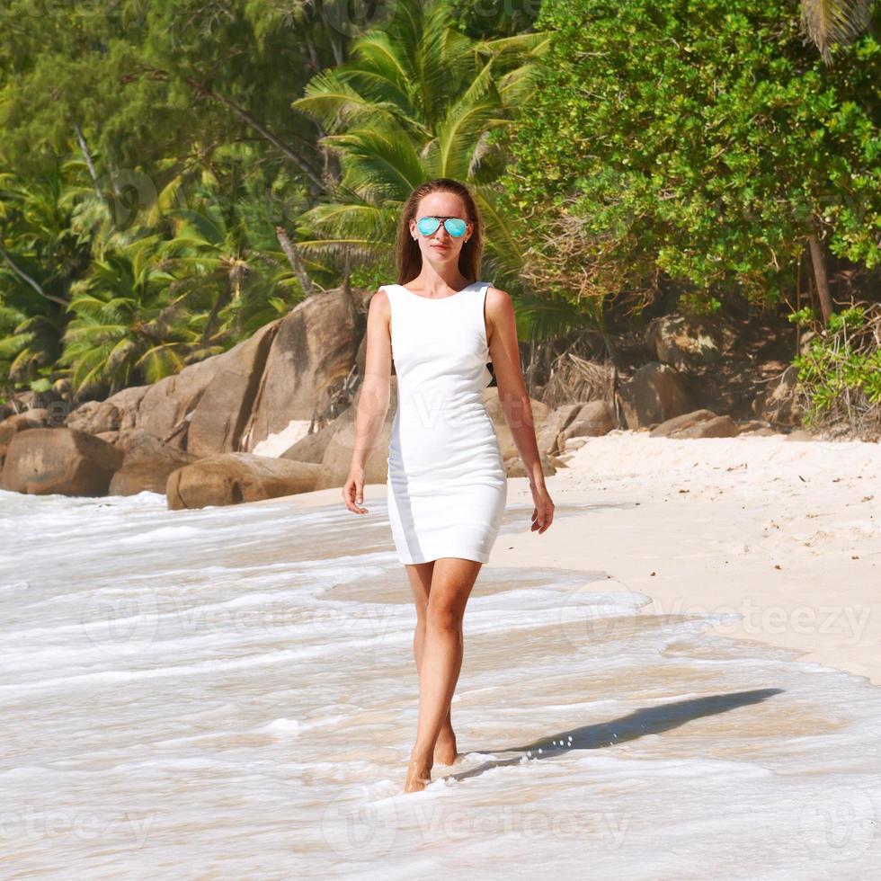 kvinna som bär klänning på stranden på seychellerna foto