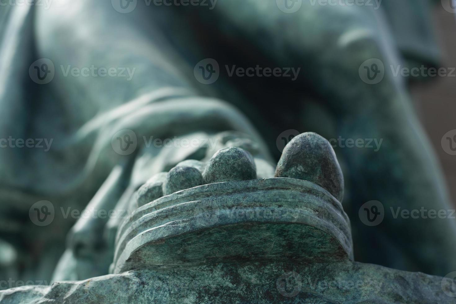 grönaktig sandad fot av en staty foto