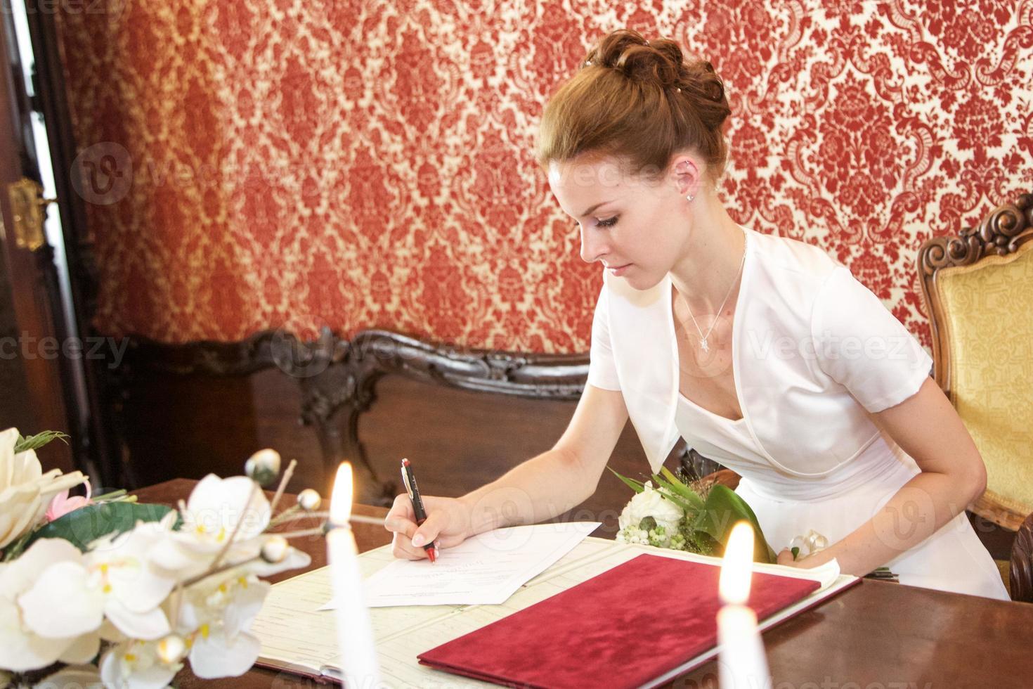 bruden undertecknar certifieringen foto